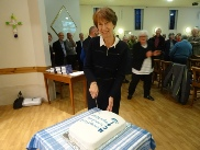 Isobel, chair of Murrayfield Churches Together, cuts the celebration cake